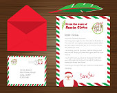 Vector illustration of a Set of Santa Claus letters, envelope and quill pen on wooden background. Includes written letter and North Pole stamp, cute Santa.  Easy to edit. Vector EPS 10.