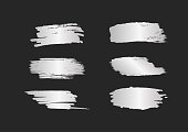 Set of silver smears. Silvery brush strokes with shine isolated on black background. Grunge, sketch, graffiti. Vector illustration.