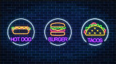 Set of three neon glowing signs of burger, hot dog and tacos in circle frames on a dark brick wall background. Fastfood light billboard symbol. Cafe menu item. Vector illustration.