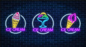 Set of three neon glowing signs of different kinds of ice cream in circle frames on a dark brick wall background. Ice-cream light billboard symbol. Cafe menu item. Vector illustration.
