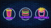 Set of three neon glowing signs of french fries, burger and soda drink in circle frames on a dark brick wall background. Fastfood light billboard symbol. Cafe menu item. Vector illustration.