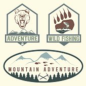set of vintage adventure labels with bear,salmon and mountains