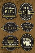 Vector illustration of a set of vintage wine labels on an oak background. Retro stylized text design and design elements and textured or worn label accents. Feature victorian style house, scrolls, ribbons and grapes on vine. Download includes Illustrator 8 eps, high resolution jpg and png file. See my portfolio for other wine and beer labels.