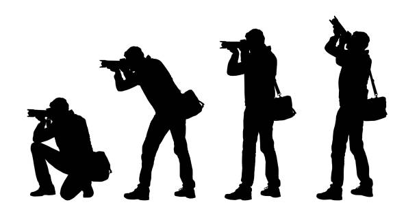 set realistic silhouettes of male photographer standing and kneeling with camera. isolated on white background - vector - fotografika stock illustrations