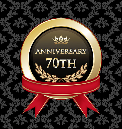 Seventieth anniversary celebration gold award with with a red ribbon on a black damask background.