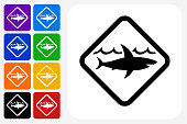 Shark Warning Sign Icon Square Button Set. The icon is in black on a white square with rounded corners. The are eight alternative button options on the left in purple, blue, navy, green, orange, yellow, black and red colors. The icon is in white against these vibrant backgrounds. The illustration is flat and will work well both online and in print.