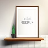 Shelf with poster mock up. Wooden shelf and print in frame on white wall with tiles and plant in ceramic black vase