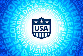 USA Shield Icon on Internet Modern Technology Words Background. This blue vector background features the main icon in the center of the image. The icon is surrounded by a set of conceptual words and technology and internet icons. The icon is highlighted by a strong starburst glow effect and stands out from the rest of the image. The technology terminology is arranged in a circular manner. The predominant tone of the image is blue with a circular gradient that originates from the center of the composition.