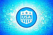 USA Shield Icon on Internet Technology Background. This image features the main icon on a blue round button. The vector button is surrounded by a seamless pattern of internet and modern technology icons. The icons vary in size. There is a glow effect around the button. Icons include such technology elements as computer, email, internet, communications and many more. The image is predominantly blue in color.