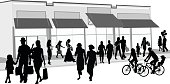 A vector silhouette illustration of people infront of a shopping mall or store.  People include a family walking and holding hands, a family riding bikes, couples holding hands, and women carrying shopping bags.