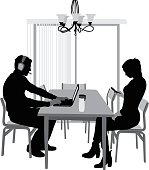 A vector silhouette illustration of two young people sharing the dining room space but not interacting.  The young man is on his lap top wearing a headset.  The young woman is focused on her cell phone.