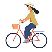 Girl in summer clothes and hat, riding a traditional bike with rack and shopping basket
