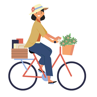 Side view of woman with shopping riding a retro bicycle