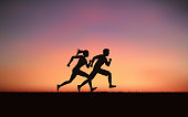 Silhouette couple man and woman sprint running on hill under sunset sky background