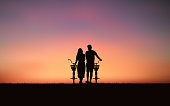 Silhouette couple man and woman walking together with bicycle under sunset sky background