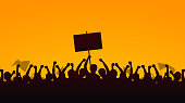 Silhouette group of people Raised Fist and Protest Signs in yellow evening sky background