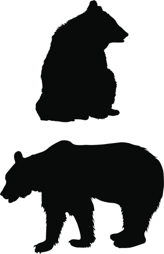 A silhouette of a bear sitting and standing