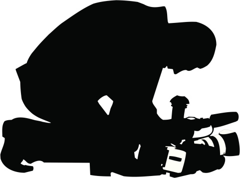 Silhouette of a camera man kneeling down with his camera