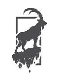 Silhouette of a mountain goat standing on a rock.