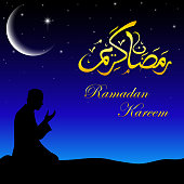 Silhouette of a Muslim praying in the when night
