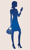 Silhouette of a woman holding a handbag and cell phone