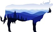 Silhouette of cow with winter mountain landscape.