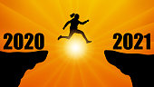 Silhouette of jumping woman over chasm between mountains. Transition from 2020 to 2021, new year. Vector illustration