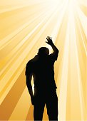 Silhouette of man praying in the midst of yellow sun rays