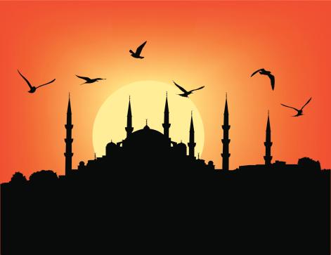 Silhouette of mosque against dark orange sunset