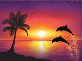 Silhouette of palm tree and dolphins.