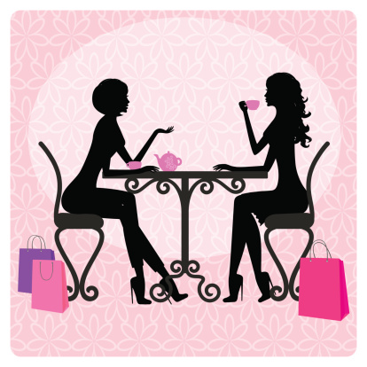 Silhouette of two beautiful girls talking in cafe