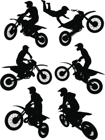 Silhouettes of a motocross rider performing stunts