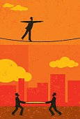 A retro businessman walking a tightrope with two men and a safety net underneath in case he falls. The people & rope and background are on separate labeled layers.