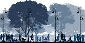 Silhouettes of people walking in a park at night