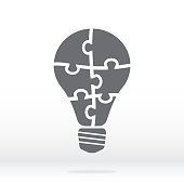 Simple icon light bulb puzzle in gray. Simple icon puzzle of the six pieces on gray background. Flat design. Vector illustration EPS10.