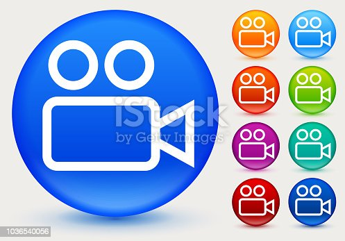 Simple Video Camera Icon. The icon is white and is placed on a round blue vector button. The button has a sight shadow and the background is light. The composition is simple and elegant. The vector icon is the most prominent part if this illustration. There are eight alternate button variations on the right side of the image. The alternate colors are orange, red, purple, maroon, light blue, green, teal and indigo.