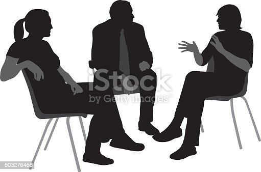 A vector silhouette illustration of a group of three people engaged in discussion incliding a young man speaking and gesturing, and a mature man and young woman listening.  They sit on chairs.