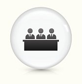 Sitting Businessmen Icon on simple white round button. This 100% royalty free vector button is circular in shape and the icon is the primary subject of the composition. There is a slight reflection visible at the bottom.