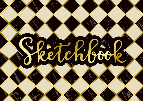 Sketchbook in golden with brown outline on textured chess board background in dark brown and ivory white