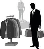 A vector silhouette illustration of a young man dressed in a suit and tie holds shopping bags in a clothing store beside a rack of mens suits and a display mannequin.