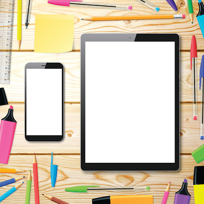 Smartphone and Tablet Pc on wooden desk with office supplies