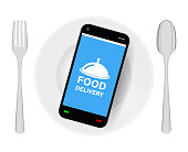 smartphone with food delivery on dish with folk and spoon