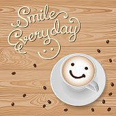 Top view of smile cappuccino with coffee beans on wooden background