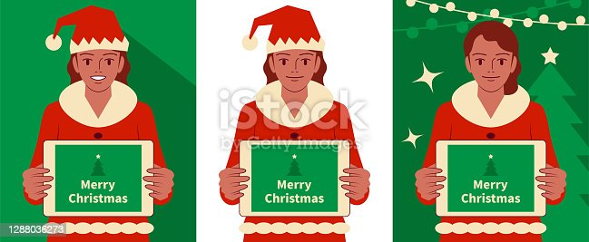 istock Smiling beautiful teenage girl dressed in a Santa Claus suit holding a digital tablet of blank screen and looking at camera 1288036273