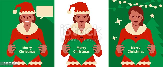 istock Smiling beautiful teenage girl dressed in a Santa Claus suit holding a heart shape sign and looking at camera 1288534395