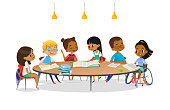Smiling disabled girl in wheelchair and her school friends sitting around round table, reading books and talk to each other. Concept of inclusive activity. Cartoon vector illustration for banner