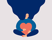 istock Smiling female character sits in lotus pose with closed eyes and eembraces a big red heart 1272652725