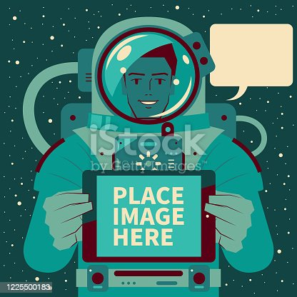 istock Smiling handsome astronaut (spaceman) holding and showing a digital tablet, Mars immigrants, Space Travel and Exploration 1225500183