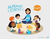 Smiling kindergarten teacher talks to children sitting in circle and