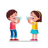 Smiling standing preschool boy and girl kids enjoying drinking water holding glasses. Children cartoon characters quenching thirst. Flat vector clipart illustration.